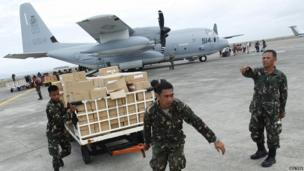Military personnel deliver aid supplies at the destroyed airport in Tacloban City, in central Philippines