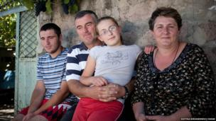 David with his wife and children in front of his mother's house in Arbo, where they have lives since fleeing the conflict in South Ossetia during the early 90's