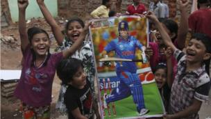 Tendulkar fans hold a poster of the cricketer in Hyderabad on 13 November 2013