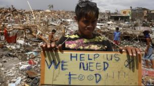 A typhoon victim holds a placard asking for food while standing amongst the ruins of houses destroyed by super typhoon Haiyan in Tanauan, Leyte in central Philippines, 14 November 2013