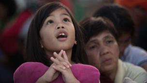 A girl watches army helicopters as they land at Tacloban airport on 14 November