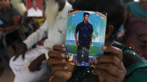 Tamils in Sri Lanka hold portraits of family members at a gathering in Colombo