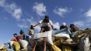 People load up sacks of rice salvaged from a destroyed rice warehouse, after super Typhoon Haiyan battered Tacloban City in central Philippines, 15 November 2013