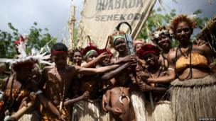 Traditionally dressed singers and dancers hold the Queen's Baton on the lagatoi, a processional canoe, that followed the relay route through the town in Port Moresby, Papua New Guinea.