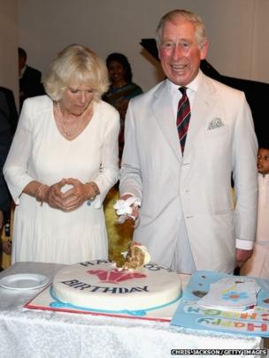 Prince Charles cuts a birthday cake alongside his wife the Duchess of Cornwall