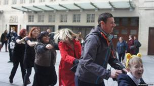 Teacher Mr Clyne and Northwood School's School Reporters in the dancing train outside Broadcasting House.