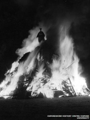 A guy dressed in academic costume burning on a bonfire, 1965