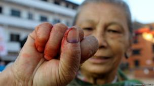 A Nepalese woman shows her inked finger after voting