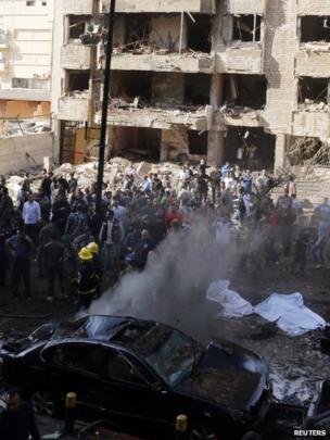 Soldiers, policemen and medical personnel gather as smoke rises from a car at the site of explosions near the Iranian embassy in Beirut, 19 Nov
