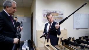 Russian Prime Minister Dmitry Medvedev holds a weapon (right) alongside his deputy Dmitry Rogozin