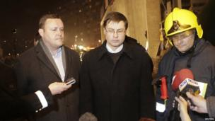Latvia's Interior Minister Rihards Kozlovskis (L), Prime Minister Valdis Dombrovskis (C) and a senior emergency services official speak to the media near the collapsed Maxima supermarket in Riga on 21 November 2013
