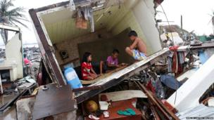 Typhoon survivors play a game called Sungka inside the bathroom of a house, toppled by Typhoon Haiyan that battered Tacloban city nearly two weeks ago, in central Philippines.