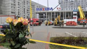 Flowers outside the collapsed Maxima supermarket in Riga, Latvia, Friday, Nov. 22, 2013