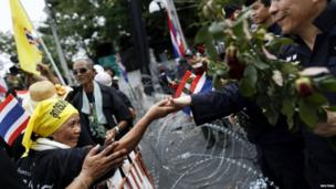 An anti-government protester touches the hand of a policemen across barbed wire after giving him flowers at a barricade near a government building chosen as a protest site in Bangkok, 25 November 2013