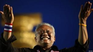 Suthep Thaugsuban, former deputy prime minister and protest leader, acknowledges the crowd at the Democracy monument in central Bangkok, where tens of thousands gathered in a protest against a government-backed amnesty bill, 24 November 2013