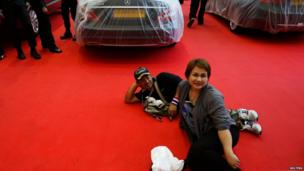 Anti-government protesters rest at a luxury car fair in Bangkok on 27 November 2013