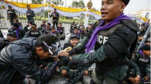 An anti-government protester shakes hands with a riot police outside the Government House during a rally in Bangkok, 3 December 2013