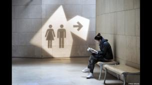 A woman reading by a toilet sign in Paris