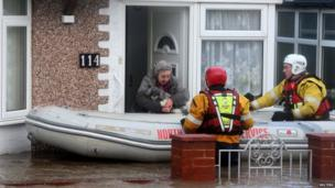 A woman and her dog led from her flooded home in Rhyl