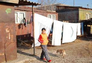 A girl walks near small iron houses on the outskirts of Gyumri on December 7, 2008.