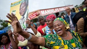 Mourners sing and dance to celebrate the life of Nelson Mandela in the street outside his old house in Soweto, Johannesburg