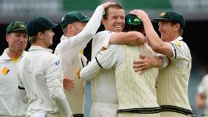 Australian fast bowler Peter Siddle (third from right) is congratulated by teammates after dismissing England batsman Stuart Broad