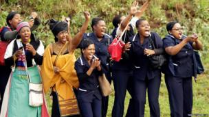 Hospital staff react as the procession for former South African president Nelson Mandela leaves the military hospital in Pretoria, South Africa