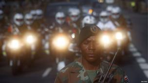 A soldier guards a closed road as military outriders escort the funeral cortege carrying the coffin of former South African President Nelson Mandela close to the Union Buildings in Pretoria December 11