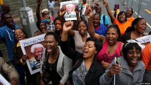 People sing and dance in the street after watching a procession carrying Nelson Mandela's coffin on 11 December