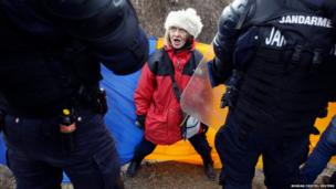 A woman argues with police in Romania