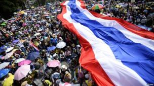 Anti-government protesters unveil a large Thai flag as they descend on Government House in Bangkok, 9 December 2013