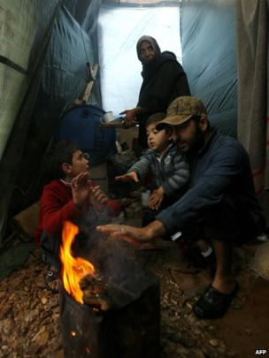 A Syrian refugee family use firewood to stay warm during rainfall in a refugee camp in the village of Ketermaya, southeast of Beirut, on December 11, 2013.
