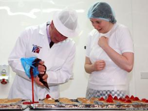 The Prince of Wales with bakery worker Lauren MacKenzie helps make strawberry tarts on a visit to Reids bakery in Thurso