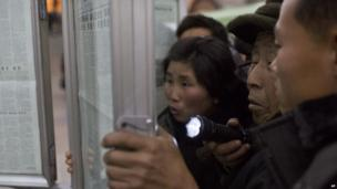 A North Korean man uses a flashlight as he and other subway commuters gather around a public newspaper stand on the train platform in Pyongyang, North Korea on 13 December 2013