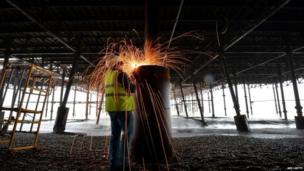 Restoration worker welding the pier column