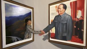 "A girl poses for a photograph next to a 3D painting of China""s late Chairman Mao Zedong at an exhibition in Binzhou, Shandong province, December 15, 2013. December 26 marks the 120th anniversary of Mao""s birth"
