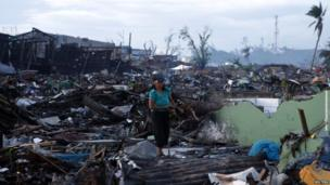 A survivor gathers firewood from the ruins of houses destroyed during last month's super typhoon Haiyan in Tacloban city