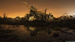 A car rests on top of a pile of debris pushed up by the wind in an area heavily damaged by the tornado in Moore, Oklahoma, 27 May 2013