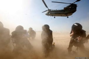 Members of the media try to protect themselves from dust blown up by a British forces transport helicopter