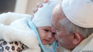 Pope Francis kisses a baby as he arrives to lead his Wednesday general audience in St Peter's Square at the Vatican