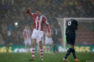 Footballer Peter Crouch shields himself from hail