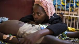 A woman sits beside her son sick with malaria at the paediatric hospital in Bangui, Central African Republic