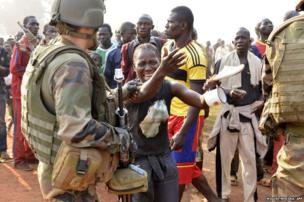 A French soldier of the Sangaris operation tries to restrain a protester crying after a demonstrator was shot dead near the international airport in Bangui