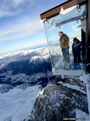 People visit the Step into the Void glass skywalk overlooking the French Alps in Chamonix