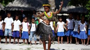 Kiribati becomes the 16th country to welcome the Queen's baton as a traditional dancer performs at Aratokotoko Primary School.