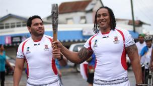 Tonga National Rugby League team members Konrad Hurrell (left) and Fuifui Moimoi (right) carry the Queen's baton in Nuku'alofa, Tonga.