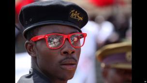 A mourner at John Nkomo's funeral in Zimbabwe wears a President Robert Mugabe designer label beret - Monday 21 January 2013