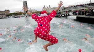 A participant in fancy dress jumps into the water during the 104th edition of the Copa Nadal (Christmas Cup) in Barcelona's Port Vell on 25 December 2013