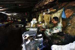 An Indian Army soldier cooks dinner in an army post in Uri, some 125 km north of Srinagar