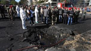 Lebanese army investigators in white coveralls stand next to a blast crater at the scene of an explosion in Beirut, Lebanon (Dec. 27, 2013)